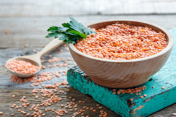 RL - Bowl with red lentils and parsley on an old wooden table